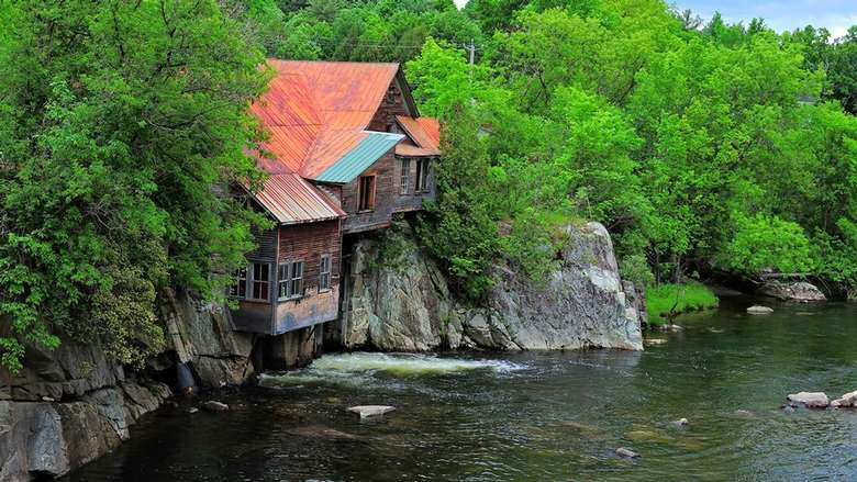 cabin with a rusty roof sitting right on the edge of a cliff