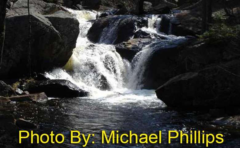 small waterfall flowing around and over rocks with photo credit to michael phillips