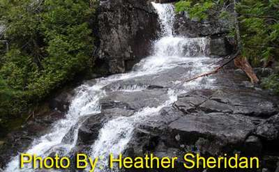 waterfall flowing over rocks with photo credit to heather sheridan