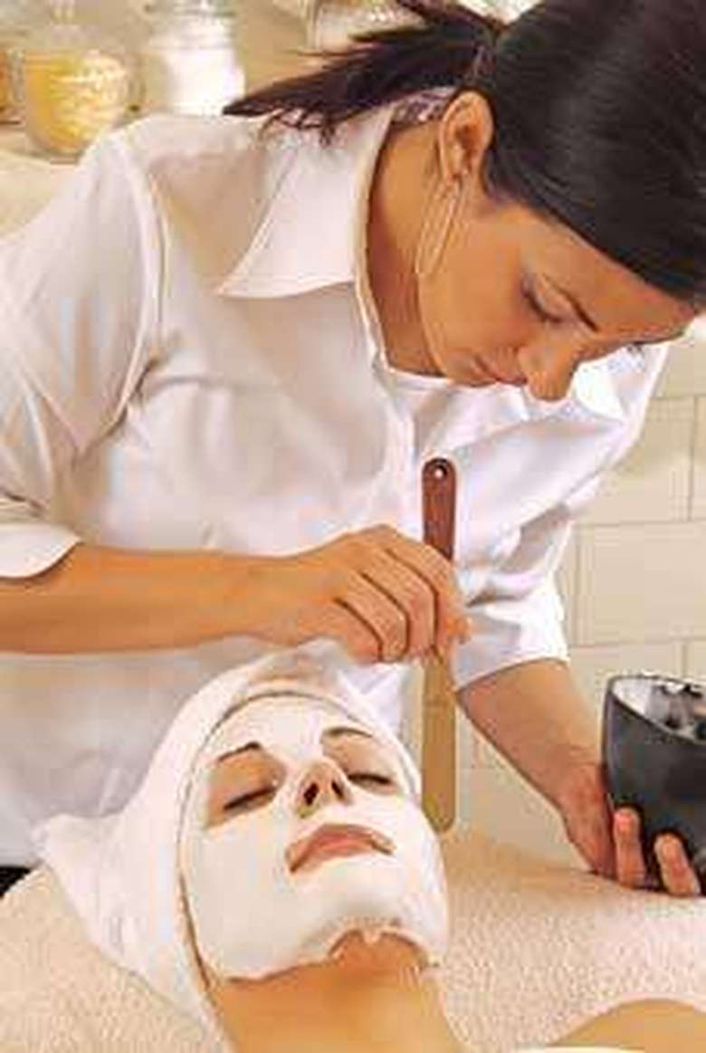 esthetician applying a facial treatment to a client