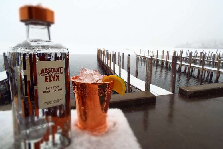 a table with a bottle of Absolute Elyx and a copper mug with a drink and slice of orange, overlooking the water and boat docks