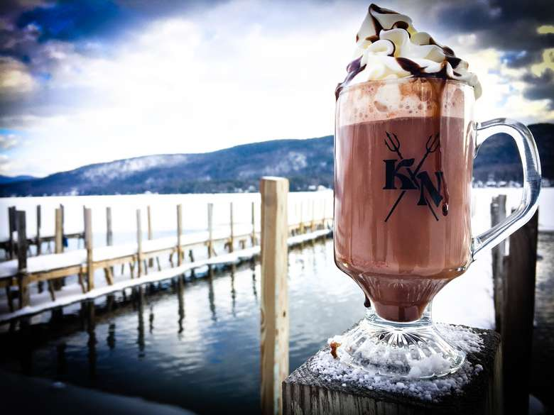 a large glass mug containing a blended drink topped with whipped cream and chocolate drizzle with the lake, boat docks and mountains in the background