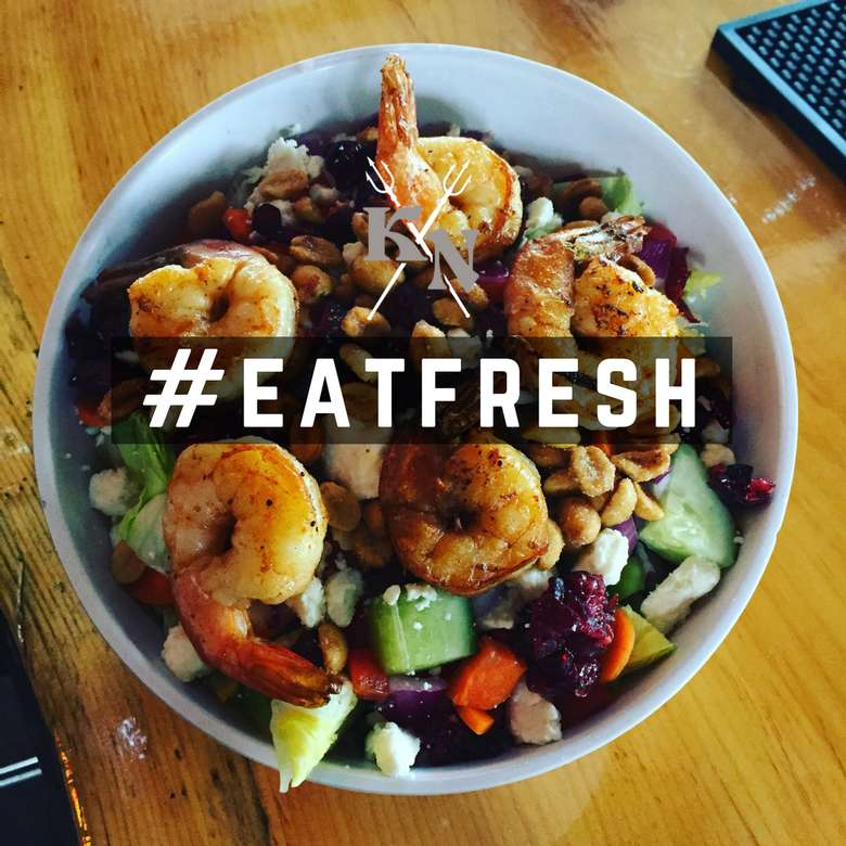 a white bowl containing a salad with shrimp and veggies with #eatfresh overlayed on the image