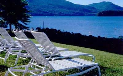 Lounge chairs on the lawn overlooking Lake George with mountains in the background