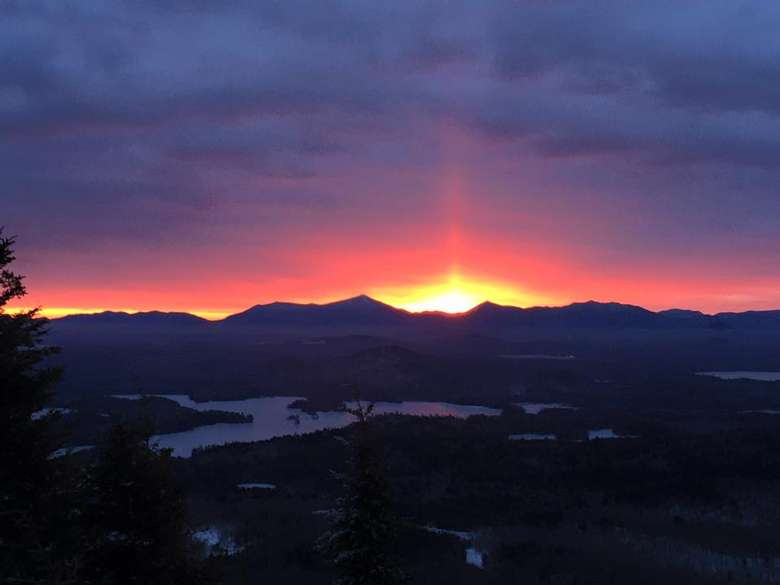 sun rising behind a distant mountain