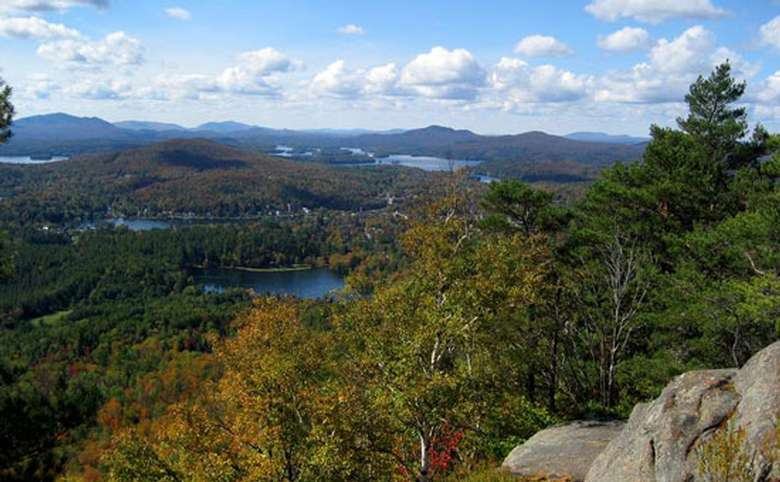 view of fall trees, mountains, and bodies of water from a mountain summit