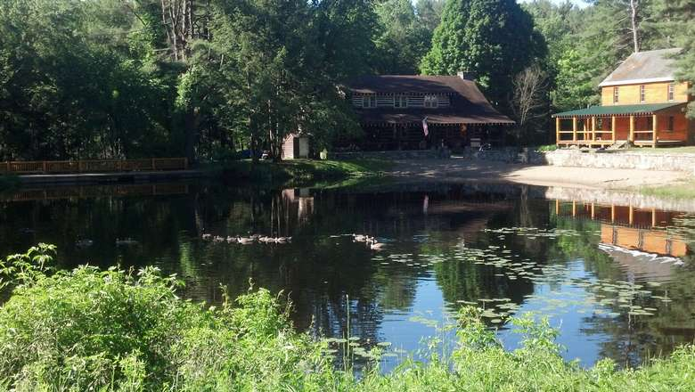 outside two large wooden houses near a pond