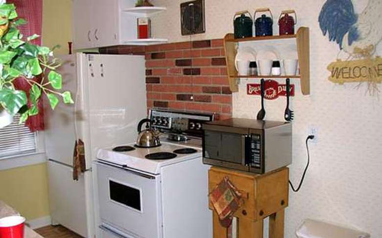 stove and refrigerator with brick work behind the stove