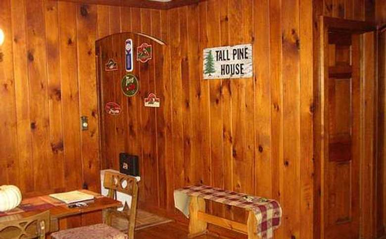 room with wood panels and a sign that says tall pine house