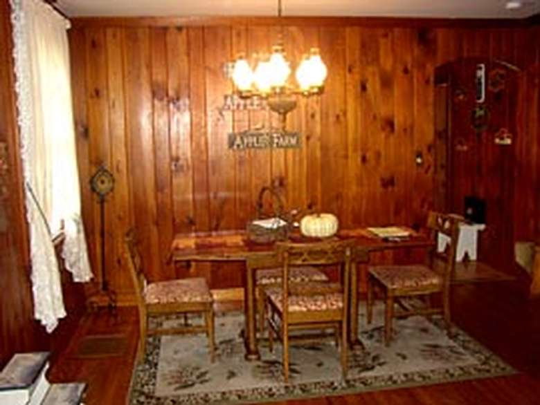 dining room table and chairs in a room with wood paneled walls
