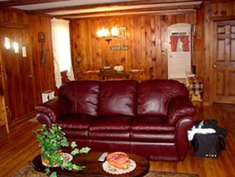 dark red leather couch in a room with paneled walls