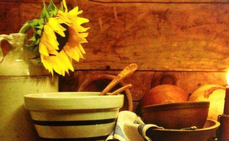 a sunflower in a jug with other kitchenware