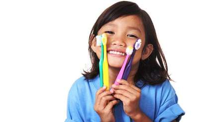 young girl holding up four colorful toothbrushes