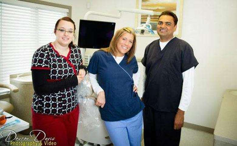 three dental assistants standing in an exam room