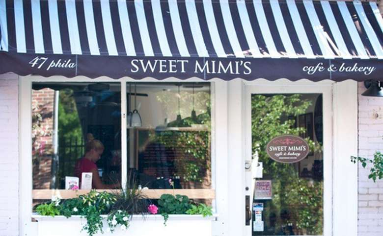 exterior of sweet mimis featuring a navy and white striped awning