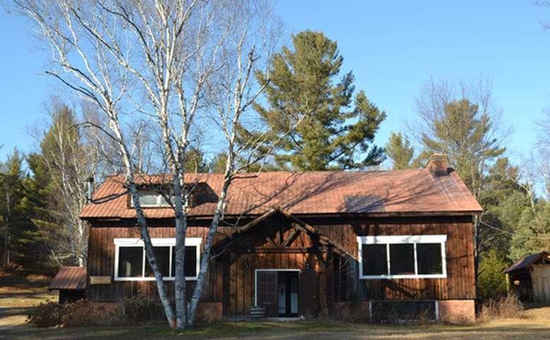brown house with white trim around the windows