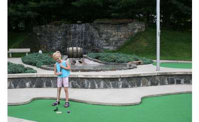 Young girl playing mini golf at Hillbilly Fun Park