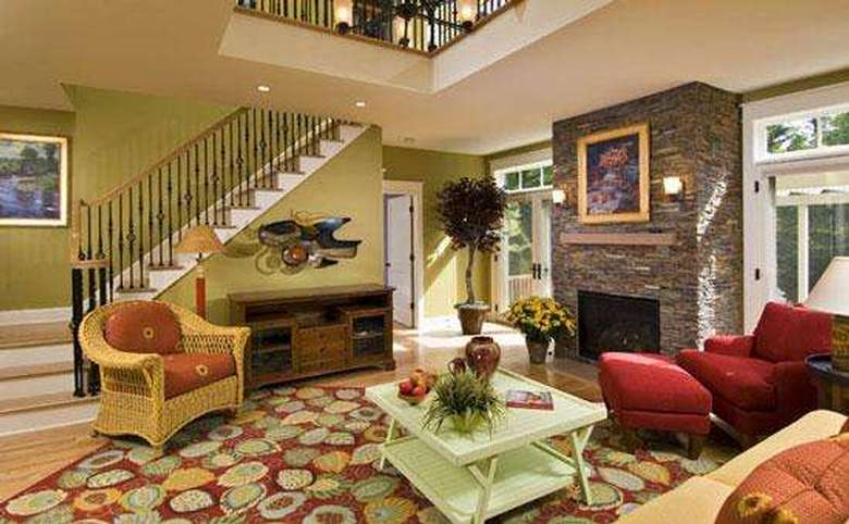 living room in a new house with a stone fireplace and large stairway