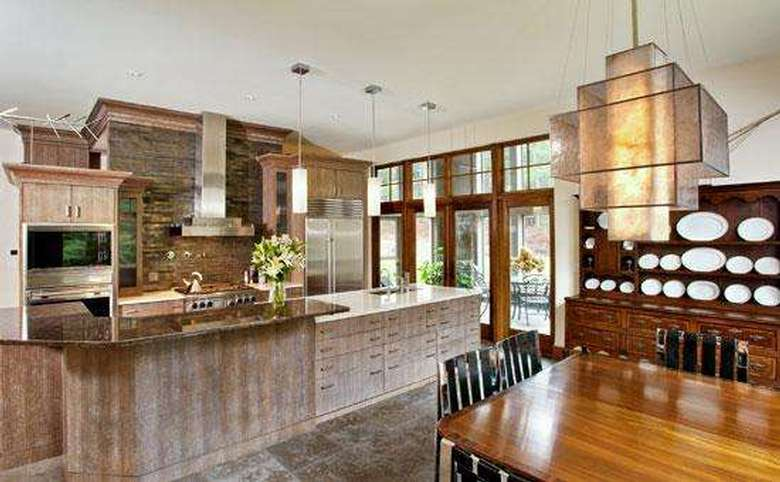 modern kitchen with a large island, stone countertops, and pendant lights