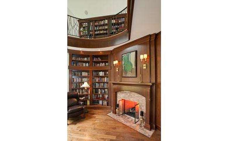 two-story library with bookshelves and a small fireplace