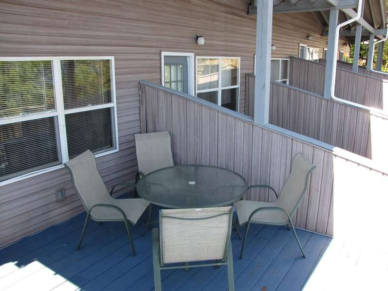 four chairs and a table on a deck with a divider between units