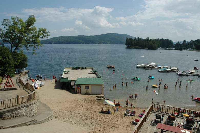 large sandy beach with boathouse and swimming area on lake george