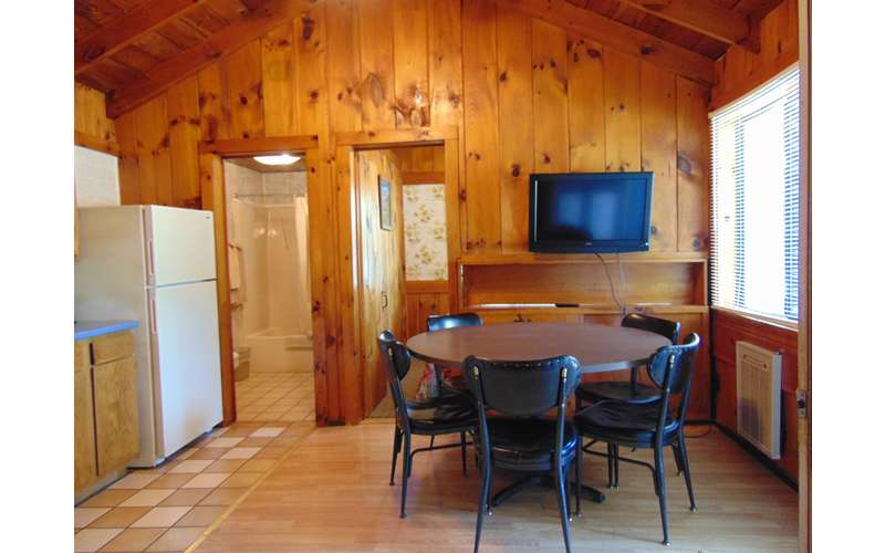 Inside Cottage With Round Table Chairs Wood Panel Walls