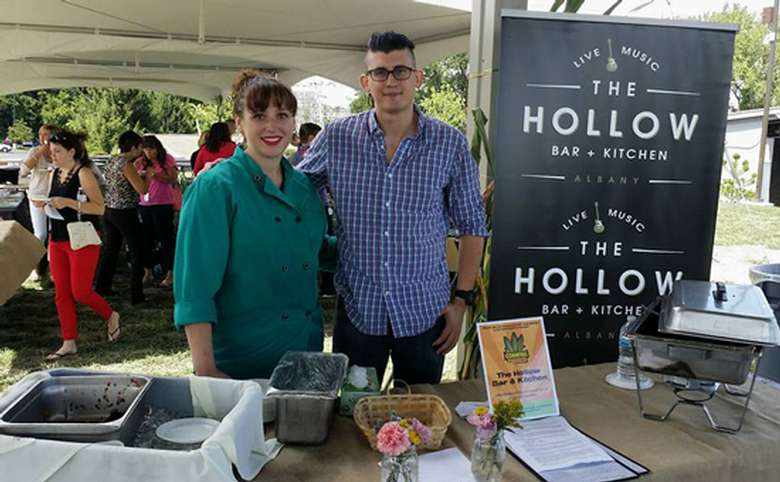 female chef and a man standing next to a sign with the hollow's logo on it at an event