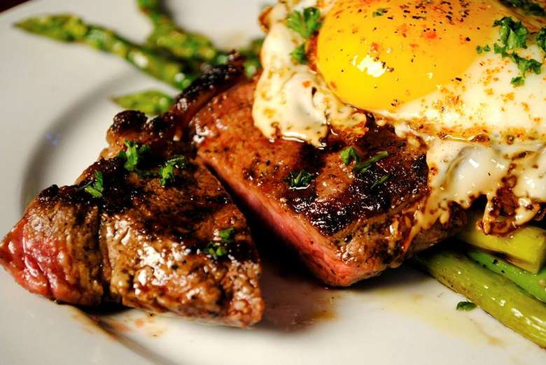 steak and eggs on a white plate with asparagus