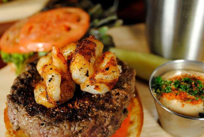 Surf + Turf Burger with a beef patty and grilled shrimp on top