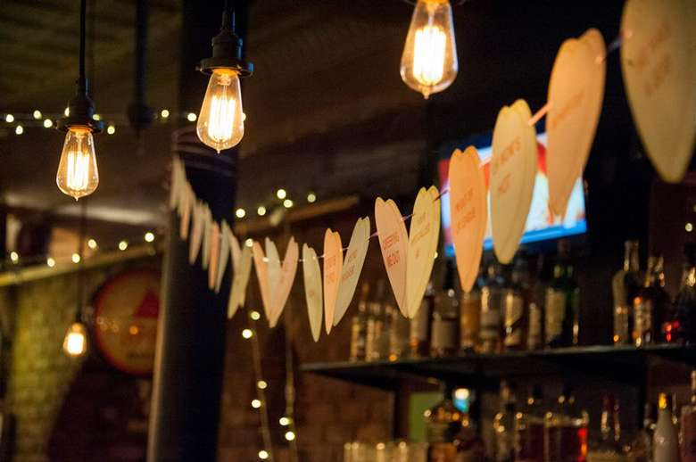string of paper hearts hanging in a bar