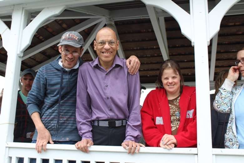 Three people in a gazebo smiling