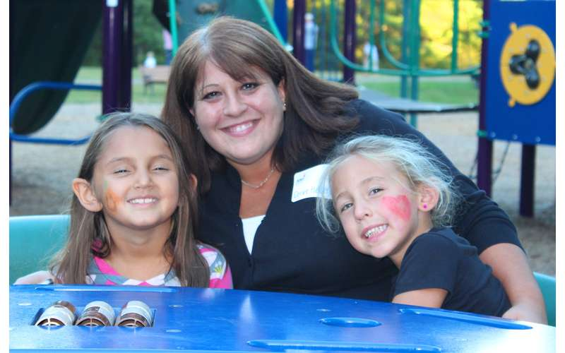 A woman and two children smiling on a playground