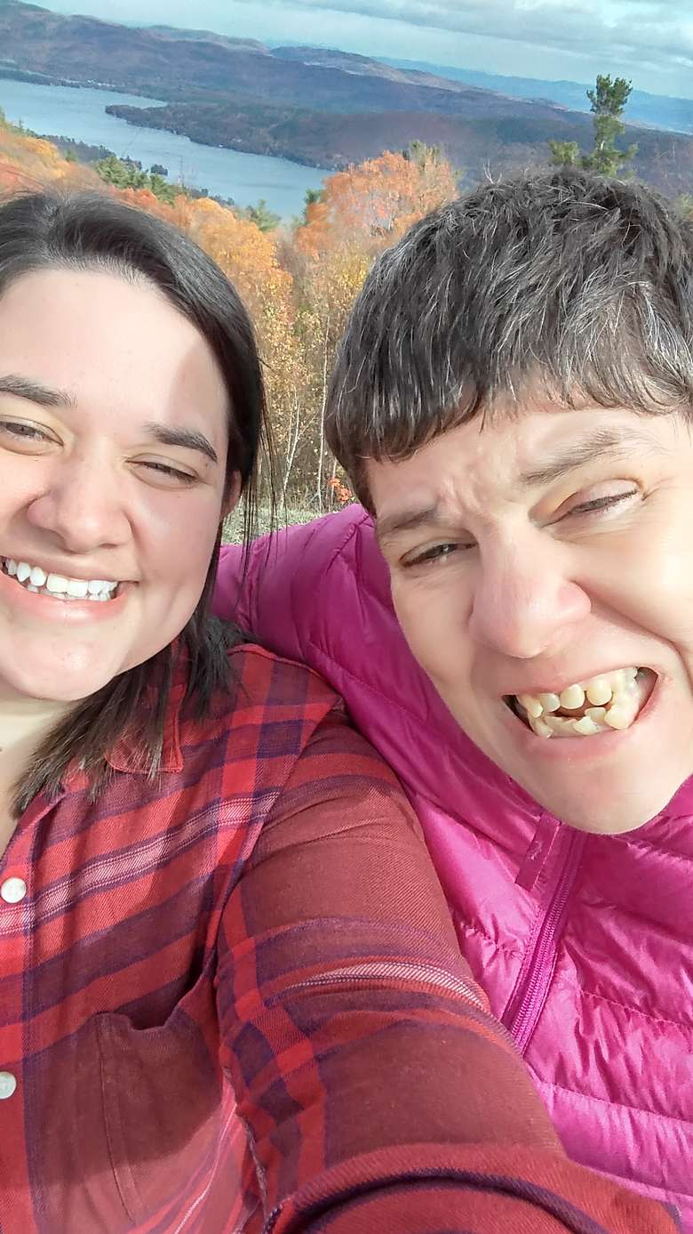 Two women smiling for the camera with a lake in the background