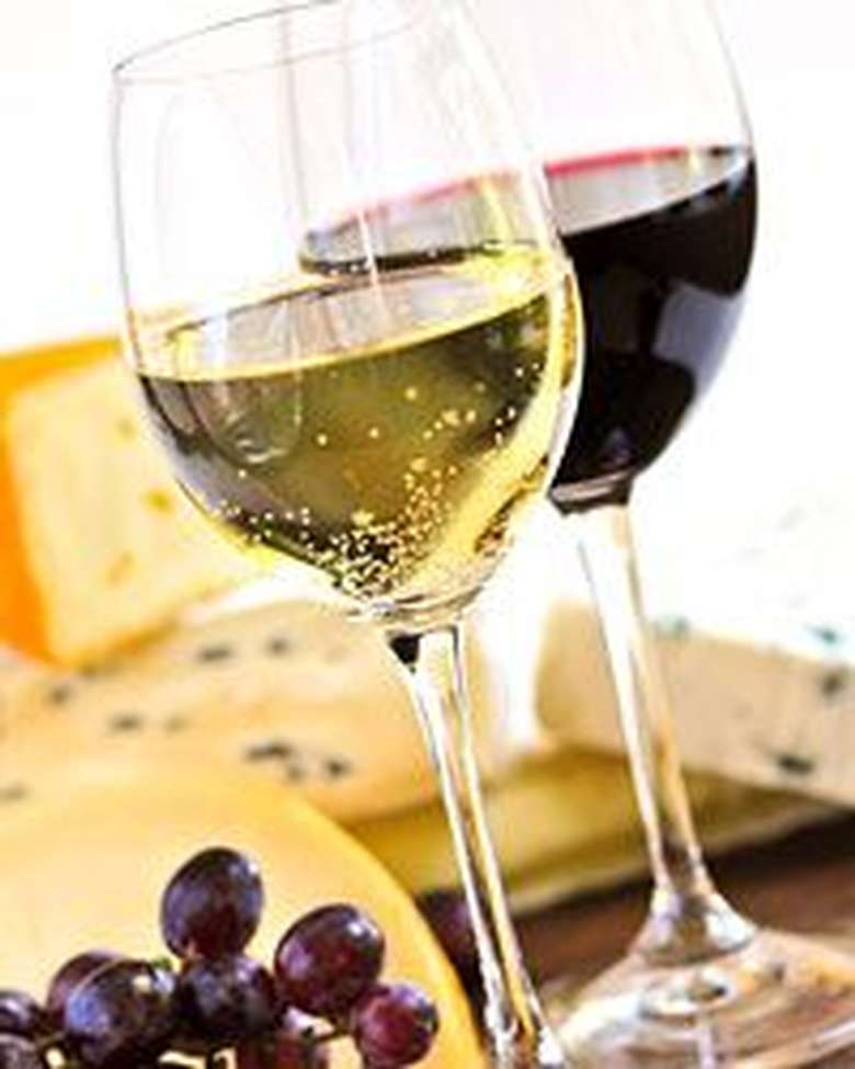 two glasses of wine, one red and one white, with blocks of cheese and grapes