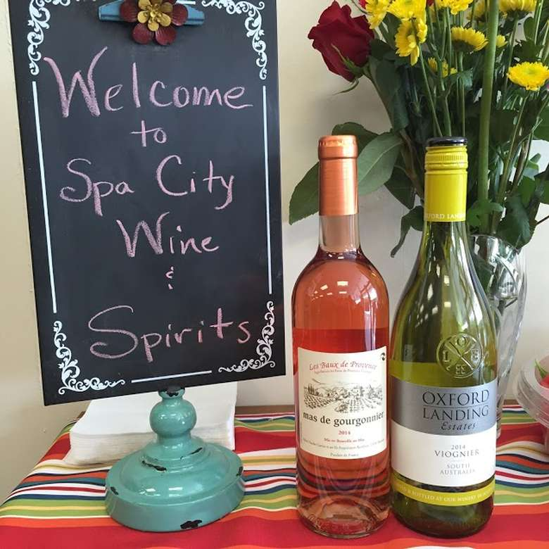 two bottles of wine, one white and one rose, with a chalkboard sign that says welcome to spa city wine and spirits