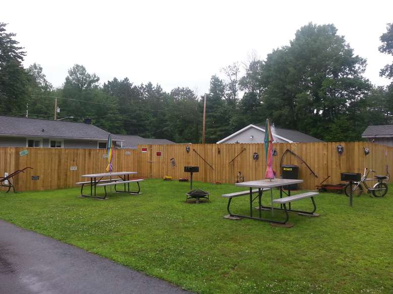 picnic tables and grills, decorative stuff hanging on a fence