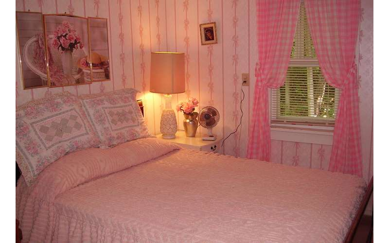 a pink themed bedroom with a bed, a lamp, and a small fan