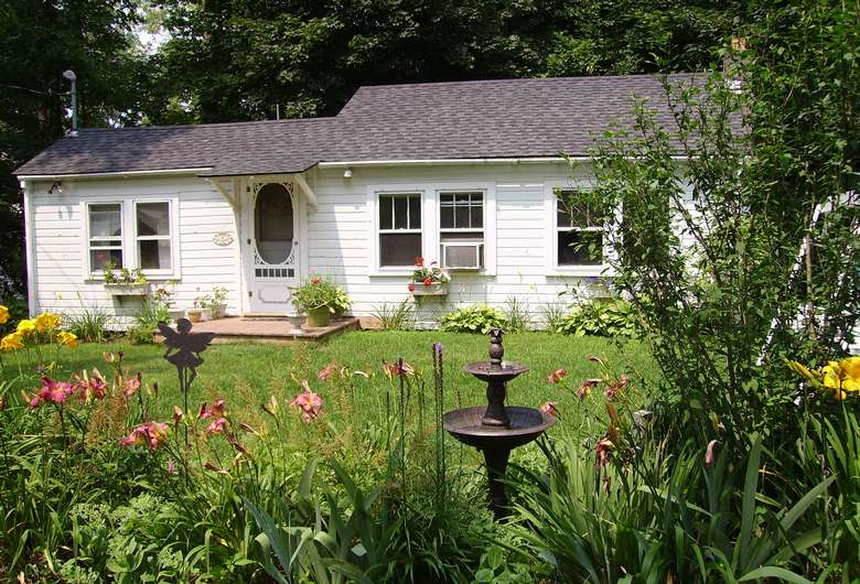 a white cottage on a lawn covered in flowers and a fountain