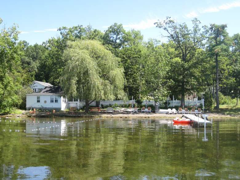 a white cottage in the background by the lakeside