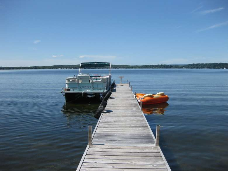 a long dock on a lake with boats on either side