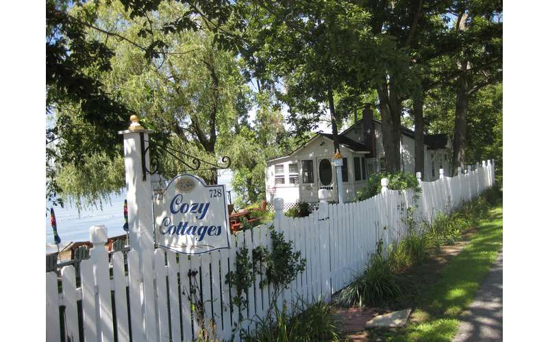 a white fence near a cottage with a sign that reads Cozy Cottages