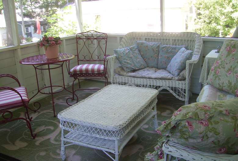 an enclosed porch with some patio furniture inside