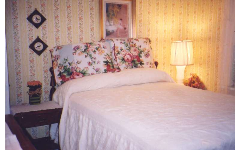 a bedroom with a bright light at one end and a bed with white blankets