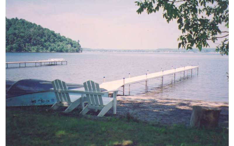 a long dock extending out from a sandy beach with adirondack chairs on it