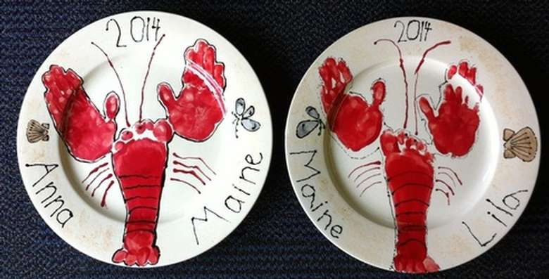 two white plates with white lobsters painted on using handprints and footprints
