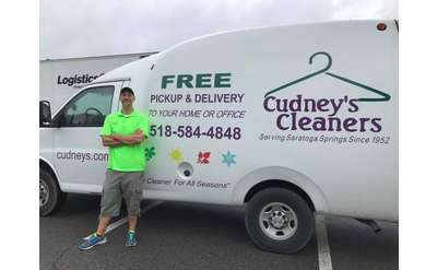 man standing near van with the cudney's cleaners logo and name