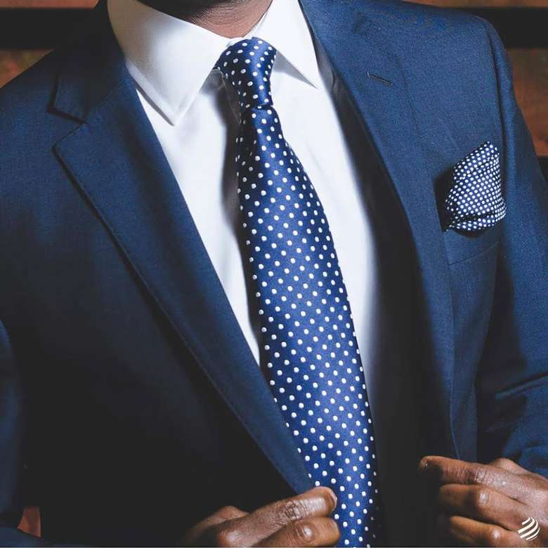 man wearing a blue suit and black and white polka dot tie
