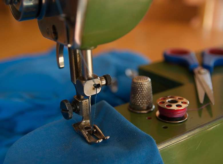 piece of a sewing machine digging into blue fabric