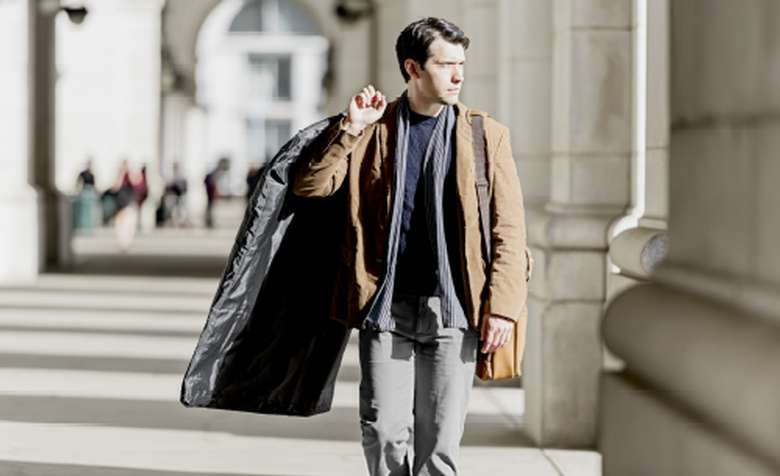 man walking and holding a black suit bag